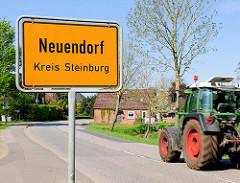 Ortsschild Neuendorf Kreis Steinburg; Trecker / Taktor auf der Strasse.