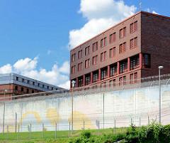 Rückseite vom Untersuchungsgefängnis am Holstenglacis in Hamburg - hohe Mauer mit Stacheldraht.