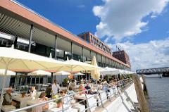 Neubauten in der Hamburger Hafencity - Elbarkaden am Magdeburger Hafen / Aussengastronomie mit Sonnenschirmen am Wasser.