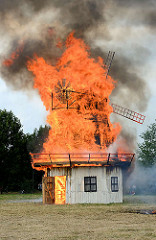 Jubiläumsfest 125 Jahre Freiwillige Feuerwehr Tangstedt - eine nachgebaute Windmühle steht in Flammen - flammen lodern hoch in den Himmel.