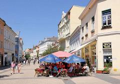 Fussgängerzone Breite Strasse in Stendal - Geschäfte, Einzelhandel. Restaurant mit Tischen unter Sonnenschirmen auf der Strasse.