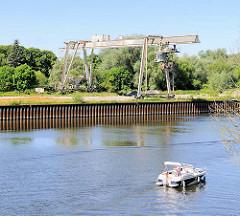 Alter Hafenkran am Ufer der Havel in Havelberg - ein Sportboot fährt flussabwärt Richtung Elbe.