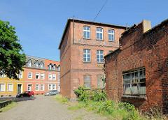 Altes leerstehendes Fabrikgebäude, Ziegelarchitektur - im Hintergrund einstöckige Wohnblocks im ausgebautem Dachgeschoss und farbigen Fassaden.
