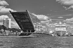 Bürogebäude Dockland am Ufer der Elbe im Hamburger Stadtteil Altona Altstadt - im Hintergrund das Kreuzfahrtschiff MSC MAGNIFICA.
