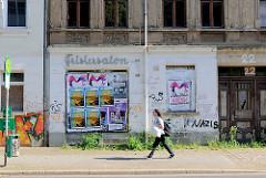 Leerstehender Frisiersalon - mit Plakaten beklebtes Schaufenster, Bushaltestelle.