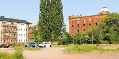 Brache in Magdeburg als Parkplatz genutzt - leerstehendes Backsteingebäude, historische Ziegelarchitektur - moderner Neubau mit Balkons / Alt + neu.