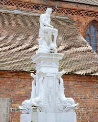 Historischer Neptunbrunnen auf dem Rathausplatz Osterburg.; im Hintergrund das Dach der Nikolaikirche.