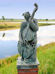 Bronzefigur mit Musikinstrument an der Wasserpromenade von Wittenberge - Skulpturengruppe Zeitreise / Künstler Christian Uhlig.