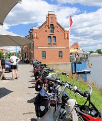 Fahrradwanderweg an der Elbe - Elberandweg in Wittenberge; Rast am Wasser - an das Geländer angelehnte, geparkte Fahrräder; im Hintergrund das historische Kranhaus der Stadt; erbaut 1884.