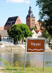 Blick über die Havel zur Stadtkirche St. Laurentius; Schild Flussname Havel.