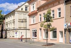 Wohnhäuser, Geschäftshäuser mit farbiger Fassade, frisch renoviert - Mann mit Hund in leerer Strasse / Wittenberge.