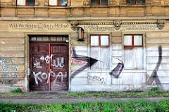 Lehrstehendes Wohnhaus in Magdeburg - mit Graffiti besprühte Hausfassade - Schilder Bau- und Möbeltischlerei - Fahrräder, Elektromaterial, Reparaturwerkstatt - Fotos aus Magdeburg.