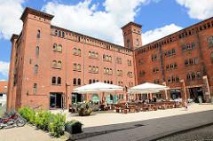Historische Industiearchitektur - Alte Ölmühle in Wittenberge, erbaut 1856 - neue Nutzung als Hotel, Restaurant und Brauerei. Aussengastronomie des Restaurants.
