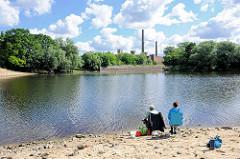 Zusammenfluss der Stepenitz und Karthane in Wittenberge - Angler sitzen am Ufer; im Hintergrund die Industriegebäude der Singer / Veritaswerke.