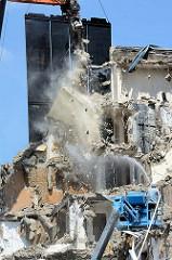 Abriss der Esso-Häuser auf Hamburg St. Pauli. Ein Arbeiter auf einer Hebebühne spritzt mit einem Schlauch Wasser auf die herabfallenden Haustrümmer.