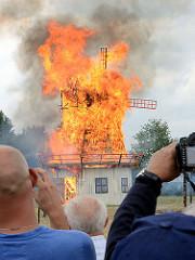 Jubiläumsfest 125 Jahre Freiwillige Feuerwehr Tangstedt - eine nachgebaute Windmühle steht in Flammen; Besucher der Veranstaltung fotografieren den Brand - flammen lodern hoch in den Himmel.