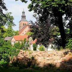 Alte Mauer in den Wallanlagen der Hansestadt Gardelegen - zwischen den Bäumen der Kirchturm der Marienkirche; Backsteingotik - Ursprungsbau aus dem 12. Jahrhundert.