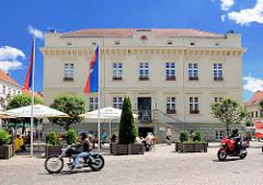 Historisches Rathaus der Hansestadt Havelberg - Restaurant mit Tischen und Sonnenschirmen auf dem Fussweg - Motorräder.