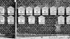 Weisse Briefkästen an einer Ziegelfassade - Schwarz-Weiss Aufnahme; Bilder aus dem Magdeburger Hafengebiet.