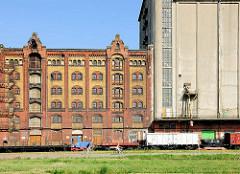Historische Speichergebäude am Kai des Handelshafen in Magdeburg - historischer Speicher, erbaut 1888. Der Handelshafen soll zum Museums- beziehungsweise Wissenschaftshafen umgebaut werden; Eisenbahnwaggons auf den Gleisen der Hafenbahn.