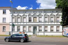 Gründerzeitgebäude / Baustil Historismus - einstöckiges Wohnhaus mit Fassadendekor - Auto mit Deutschlandfahnen.