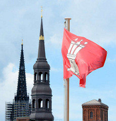 Hamburg Flagge im Wind - rote Fahne mit weissem Wappen; Kirchtürme St. Katharinen und St. Nikolai mit Baugerüst.