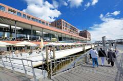 Neubauten in der Hamburger Hafencity - Elbarkaden am Magdeburger Hafen / Aussengastronomie mit Sonnenschirmen am Wasser; Anleger Maritimes Museum für Fahrgastschiffe.