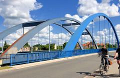Strassenbrücke und Eisenbahnbrücke über die Stepenitz in Wittenberge - blauer Himmel, weisse Wolken; Fahrradfahrer.