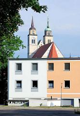 Schlichter Neubau mit unterschiedlich farblich gestalteter Fassade - Kirchtürme der Magdeburger Johanniskirche, erbaut 1238.