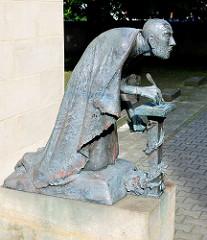 Bronzeskulptur bei der Petrikirche in Magedeburg - Schreiber mit Tintenfass.
