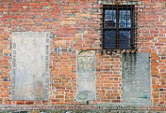 Historische Grabplatten eingelassen in die Ziegelmauer der St. Nikolai-Kirche von Osterburg.
