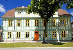 Restauriertes Fachwerkhaus in der Domherrnstrasse in der Hansestadt Havelberg - mintgrün abgesetzte Holzbalken, Fachwerk - orangenfarbene Eingangstür.