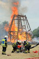 Jubiläumsfest 125 Jahre Freiwillige Feuerwehr Tangstedt - eine nachgebaute Windmühle steht in Flammen; flammen lodern hoch in den Himmel; Feuerwehrleute schliessen für die Löscharbeiten eine Wasserpumpe an.