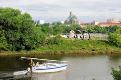 Segelboote fährt mit Motorkraft auf der Zollelbe in Magdeburg, ein Schlauchboot im Schlepp - im Hintergrund die Wallonerkirche.