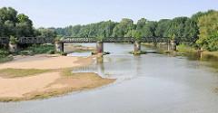 Alte Eisenbahnbrücke über die Alte Elbe in Magdeburg - Sandbank, Bäume am Flussufer.