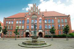 Bürgerschule / Jahnschule in Wittenberge; Backsteingebäude Neogotik - im Vordergrund Brunnen mit Gedenktafel für Friedrich Ludwig Jahn.