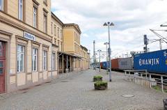 Bahnsteig und Empfangsgebäude Bahnhof Wittenberge - ein Containerzug fährt am Bahnsteig.