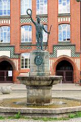 Bürgerschule / Jahnschule in Wittenberge; Backsteingebäude Neogotik - im Vordergrund Brunnen mit Gedenktafel für Friedlich Ludwig Jahn.