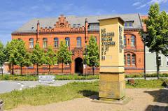 Backsteinarchitektur Neogotik in Osterburg - Gebäude, Sitz vom Arbeitsamt; Erinnerungsstelle Aufschrift: DIE MENSCHEN MÜSSEN SPRECHEN - NICHT DIE WAFFEN.