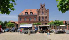 Architekturbilder Backsteingebäude - neogotische Architektur; ehem. Postgebäude in der Hansestadt Seehausen, zum Wohnhaus umgebaut; Imbissstände auf dem Platz.