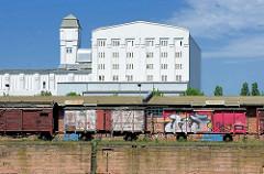 Eisenbahnwaggons mit Graffiti - Industriearchitektur, weisse Fassade; Gewerbegebiet am Handelshafen.