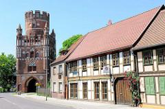 Uenglinger Tor - historisches Stadttor, erbaut um 1460. Fachwerkhäuser, blühendender Rosenstrauch am Eingang - Strasse Altes Dorf.
