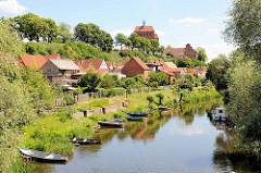 Blick über den Stadtgraben in der Hansestadt Havelberg - Holzkähne am Ufer; Häuser mit Gärten am Wasser; im Hintergrund der Havelberger Dom St. Marien.