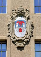 Stuckdekor an der Fassade des Pestalozzi-Gymnasiums; Wappen von Havelberg, Jahreszahlen 1912 - 2013.