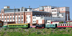 Industriearchitektur im Magdeburger Hafengebiet - Ziegelgebäude mit weiss abgesetzter Fassade der 1930er Jahre - historische Eisenbahnwaggons, Lokomotive.