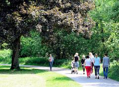Spazierweg unter Bäumen am Ufer der Wandse in Hamburg Wandsbek - Spaziergängerinnen in der Sonne.