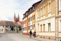 Wohnhäuser in unterschiedlichem Architekturstil in der Maxim Gorki Strasse von Kyritz - im Hintergrund die Kirchtürme der Pfarrkiche St. Marien.