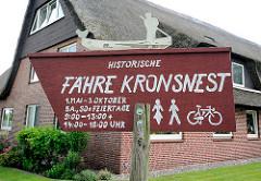 Hinweisschild in Seestermühe - Historische Fähre Kronsnest mit Öffnungszeiten.