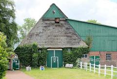 Historischer Bauernhof mit Reetdach und Efeufassade in Seestermühe, Kreis Pinneberg.