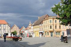 Marktplatz von Kyritz - historische Wohnhäuser, Geschäftshäuser - dunkler Gewitterhimmel über der Stadt.